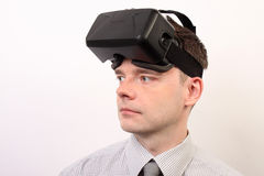 Opinião dianteira um homem que veste uns auriculares da falha 3D de Oculus da realidade virtual de VR, cara que olha à esquerda Imagens de Stock Royalty Free