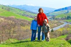 Opinião do país da montanha da família e da mola do turista Imagem de Stock Royalty Free