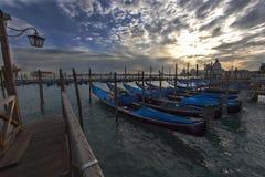 Opinião do por do sol de Santa Maria della Salute de Veneza com fileira de barcos da gôndola Imagens de Stock