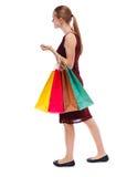 Opinião lateral a mulher indo com sacos de compras Imagem de Stock Royalty Free