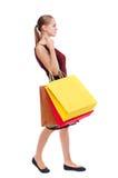 Opinião lateral a mulher indo com sacos de compras Fotos de Stock