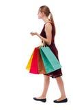 Opinião lateral a mulher indo com sacos de compras Foto de Stock Royalty Free