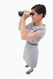 Opinião lateral a mulher que usa spyglasses Foto de Stock Royalty Free