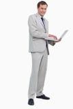 Opinião lateral o homem de negócios de sorriso que usa seu portátil Imagem de Stock