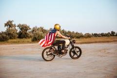 Opinião lateral o homem no cabo da bandeira americana que conduz a motocicleta Imagens de Stock Royalty Free