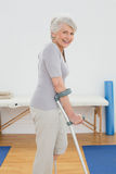 Opinião lateral uma mulher superior de sorriso com muletas Imagem de Stock Royalty Free