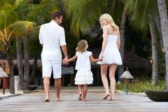 Opinião traseira a família que anda no molhe de madeira Fotografia de Stock