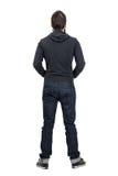 Opinião traseira o homem na camisa encapuçado preta com rolado acima das calças de brim Foto de Stock