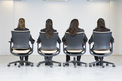Opinião traseira quatro mulheres de negócio que sentam-se no escritório Fotografia de Stock Royalty Free