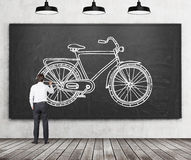Opinião traseira um homem de negócios na roupa formal que esteja tirando um esboço de uma bicicleta no quadro preto enorme Um con Foto de Stock