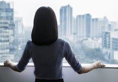 Opinião traseira uma mulher de negócios que olha para fora a janela na arquitectura da cidade no Pequim, China Imagens de Stock