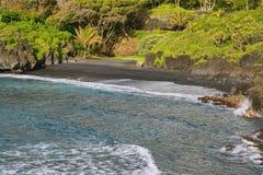 Opiniones negras de la playa de la arena en parque de estado de Waianapanapa Imagen de archivo libre de regalías