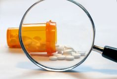 Opioid Crisis - Open Bottle of Prescription Painkillers. Open Bottle of Prescription Drugs with a Magnifying Glass in front enlarging them stock photos
