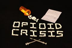 Opioid Crisis spelled out, prescription, pills and needles. A bottle of spilled pills next to a prescription with opioid crisis spelled out with white pills on a royalty free stock photos