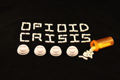 Opioid crisis spelled out with white pills above several prescription bottle lids on a black background. Opioid crisis is spelled out with white pills above four stock image