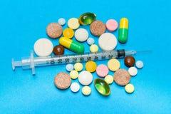 Opioid epidemie Opioid Pillen Druggebruik Concept - verschillende gekleurde pillen en spuit op een blauwe achtergrond stock afbeelding