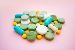 Opioid Pills. Opioid epidemic and drug abuse concept. Different. Tablets, pills, capsule on a pink background. Heap mix therapy drugs Stock Photos