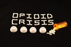 Opioidkris som ut stavas med vita preventivpillerar ovanför flera receptflasklock på en svart bakgrund Fotografering för Bildbyråer