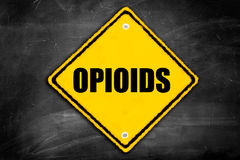 Opioids written on caution sign. On a black chalkboard with room for print Stock Images