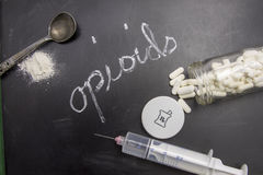 Opioids. Written in chalk on blackboard with crushed powder, spoon, syring and prescription vial Royalty Free Stock Photos