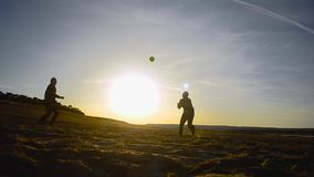 Opleidende mensen in volleyball op strand in de zon, strandvolleyball op zand op de lenteavond stock footage