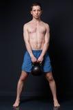 Opleiding met gewichten Sterke mens die een kettlebell tussen y houden royalty-vrije stock afbeeldingen