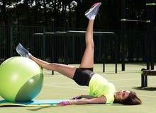 Opleiding op de geschikte bal Jonge vrouw die sportenoefeningen op een bal voor opleiding doen stock afbeelding