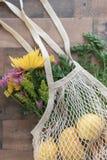 Opnieuw te gebruiken brei zak met opbrengst en verse bloemen stock fotografie