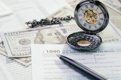 Opodatkowywa czas w Kwietnia pojęciu, pióro na 1040 USA podatku dochodowego plombowania indywidualnej formie z rocznika kieszenio obrazy stock
