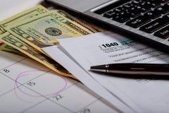 Opodatkowywa dni dolary i tworzy 1040 podatek dochodowy formy seansu podatku dzień dla Kwietnia kalendarza z słowami obraz royalty free