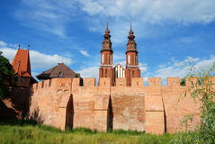 Opole, Poland: Medieval Walls and Cathedral. Finely reconstructed brick medieval city defense walls with crenellations and twin towers of nearby Holy Cross stock image