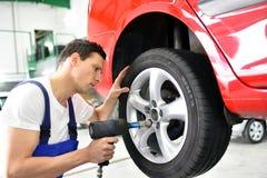 Opony zmiana w samochodowym remontowym sklepie - pracownik gromadzić obręcze na zdjęcie stock