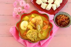 Opor ayam. Indonesian food, Opor ayam, Chicken cooked in coconut milk and spices served with lontong and sambal royalty free stock photo