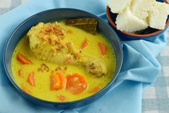 Opor ayam. Indonesian food. Chicken cooked in coconut milk and spices. Served with rice cake Stock Photo