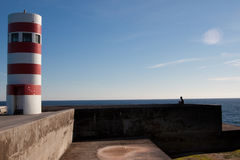 Oporto lighthouse. Red and white lighthouse and small men silhouette against the atlantic ocean in the city of Oporto, Portugal royalty free stock photo