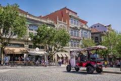 OPORTO, PORTUGAL - 25 DE ABRIL DE 2018: Tuk-tuk en la calle con la biblioteca y la librería famosas Livraria Lello en Oporto imagenes de archivo