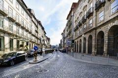Oporto, Portugal 12 de agosto de 2017: La calle central de la ciudad de par en par y cobbled con los guijarros con las fachadas d Fotografía de archivo libre de regalías