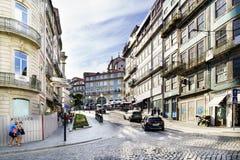 Oporto, Portugal 12 de agosto de 2017: La calle central de la ciudad de par en par y cobbled con los guijarros con las fachadas d Foto de archivo libre de regalías