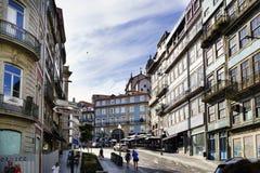 Oporto, Portugal 12 de agosto de 2017: La calle central de la ciudad de par en par y cobbled con los guijarros con las fachadas d Foto de archivo