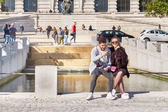 OPORTO, PORTUGAL - 26 DE MARZO DE 2018: Junte sentarse en un banco, una muchacha sonriente y un individuo con Internet de la ojea foto de archivo libre de regalías