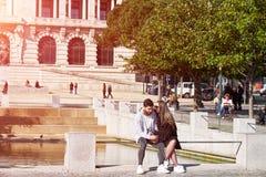 OPORTO, PORTUGAL - 26 DE MARZO DE 2018: Pares jovenes que se sientan en un banco, individuo con Internet de la ojeada en smartpho fotografía de archivo libre de regalías