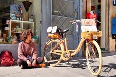 OPORTO, PORTUGAL - 26 DE MARZO DE 2018: Retrato de la mujer sonriente en la calle con la bicicleta, tienda del ` s del artista imagen de archivo