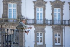 View at the Women talking on balcony on Porto Cathedral , Sé do Porto, episcopal palace of Porto as background royalty free stock images