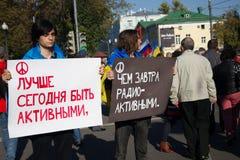Oposición desconocida con los carteles - es mejor ser el hoy activo que mañana radiactivo Imágenes de archivo libres de regalías