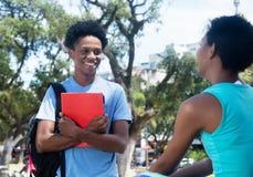 Opowiadać amerykanin afrykańskiego pochodzenia samiec i żeńskiego ucznia na kampusie un Fotografia Royalty Free