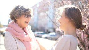 Opowiadać macierzystej i dorosłej córki na ulicie w wiośnie Jaskrawy ranku słońce, matka dzień, córka dzień zbiory wideo