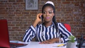Opowiadający afrykańskiej dziewczyny która fosuced na rozmowie telefonicznej relaksował podczas gdy siedzący w czerwonym studiu