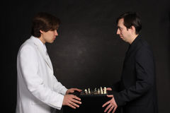 Opponents. Confrontation between two businessmans in white and black suits Royalty Free Stock Photos