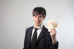 Opportune offer. Portrait of a smiling businessman showing some banknotes Stock Photos