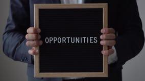 Opportunità di parola dalle lettere sul bordo del testo in uomo d'affari anonimo Hands video d archivio